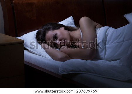 Woman lying in bed with opened eyes - stock photo