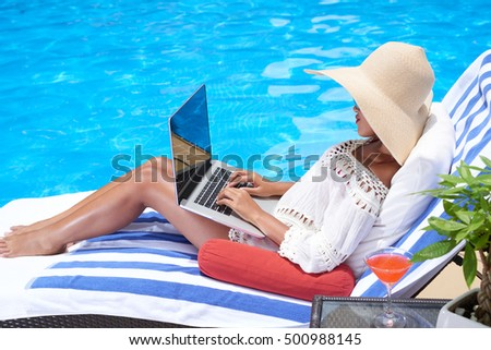 Woman lying in chaise-lounge and working on laptop