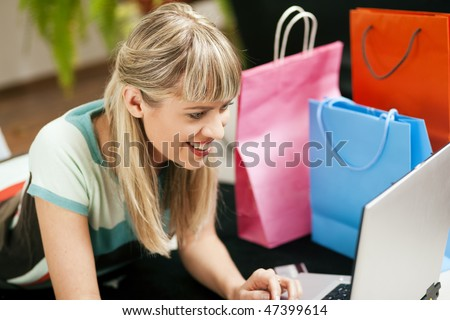 Woman lying in her home living room on floor shopping or doing banking transactions online in the Internet, emphasized by shopping bags in the background - stock photo