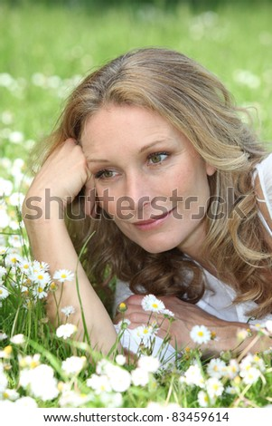 Woman lying in the daisies - stock photo