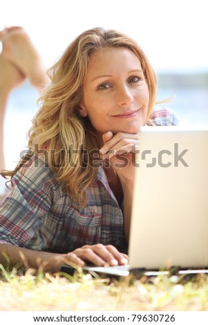 Woman lying in the grass using a laptop computer - stock photo
