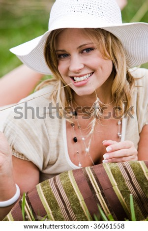 Woman lying in the grass with a pillow, holding a piece of wild grass in her mouth - stock photo