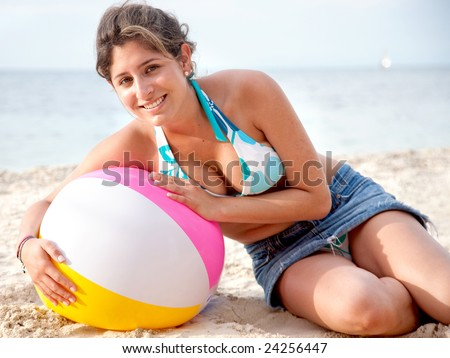 Woman lying on a ball at the beach
