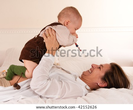 Woman lying on a bed playing with her baby boy - stock photo