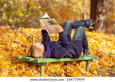 woman lying on a bench in autumn park and reading a magazine