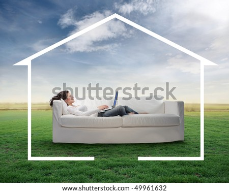 Woman lying on a couch on a green meadow and working on a laptop - stock photo