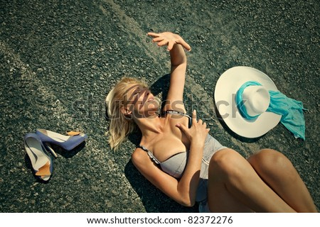 Woman lying on a desert road shielding sun with hand - stock photo