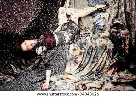 Woman lying on a pieces of colorful fabrics - stock photo