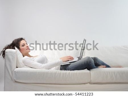 Woman lying on a sofa and using a laptop