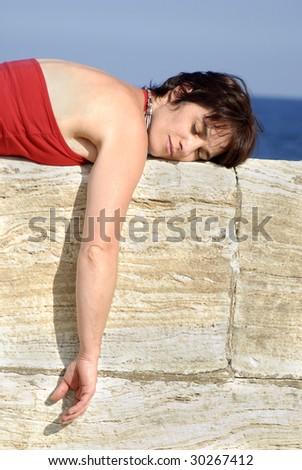 woman lying on a stone wall - stock photo