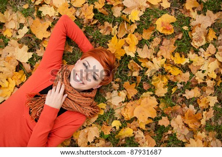 woman lying on autumn leaves, outdoor portrait - stock photo
