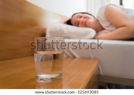 woman lying on bed with glass of mineral water on the nightstand - stock photo