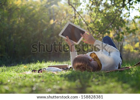 woman lying on bedding on green grass with tablet during picnic in the park - stock photo
