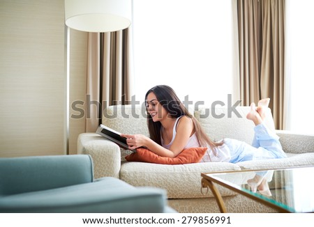 Woman lying on couch with ankles crossed reading a magazine and smiling. - stock photo