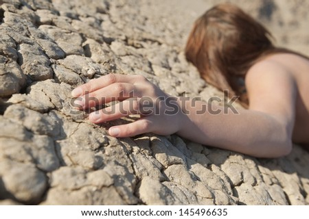 Woman lying on cracked land with focus on hand - stock photo