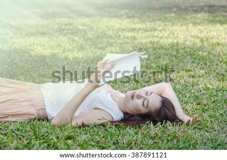 Woman lying on grass field for reading in the park - stock photo