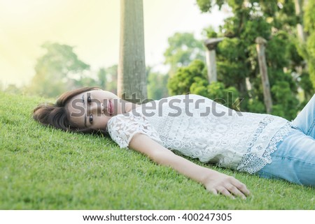 Woman lying on grass field in the park