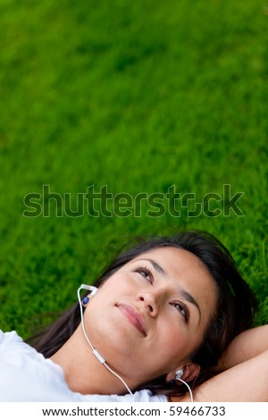 Woman lying on grass listening to music outdoors - stock photo