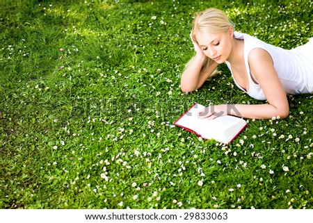Woman lying on grass, reading book - stock photo