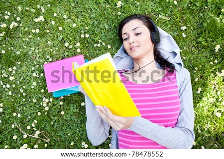 woman lying on grass with book and listening music on headset - stock photo