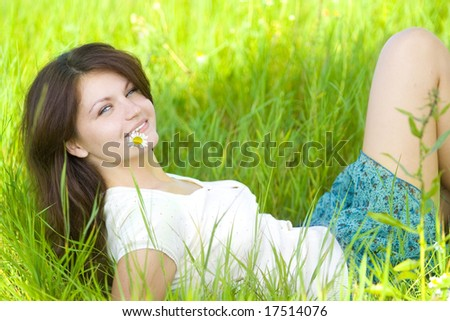 woman lying on grass with camomile - stock photo