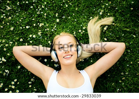 Woman lying on grass with headphones - stock photo
