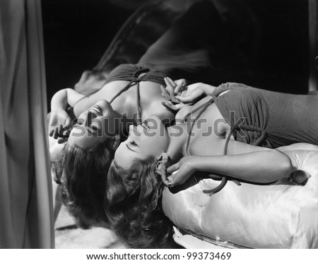 Woman lying on her back next to mirror - stock photo