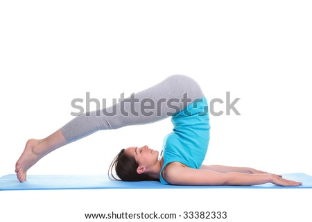 Woman lying on her back on an exercise mat in a yoga position feet over her head, isolated on a white background. - stock photo