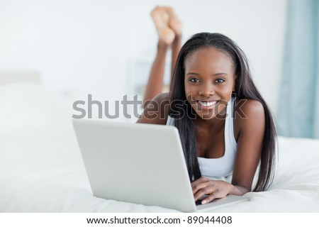 Woman lying on her belly with a laptop in her bedroom - stock photo