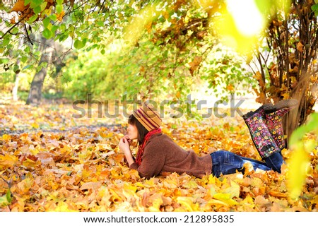Woman lying on her stomach on autumn leaves in park, side view. - stock photo