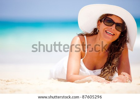 Woman lying on sand at the beach and smiling - stock photo