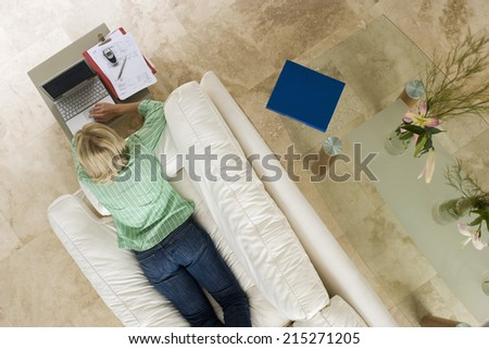 Woman lying on sofa at home, using laptop resting on coffee table, overhead view - stock photo