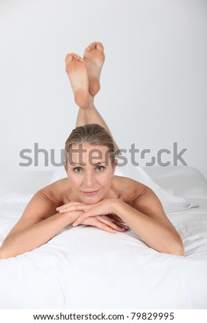 Woman lying on the bed - stock photo