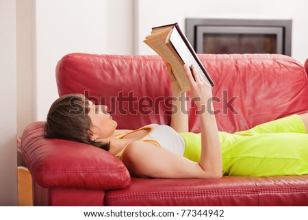 Woman lying on the couch and reading a hardcover book