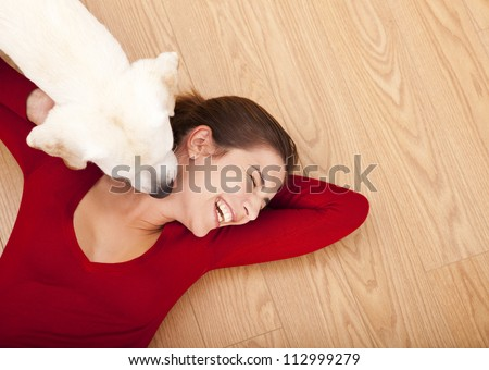 Woman lying on the floor and her dog licking her face - stock photo