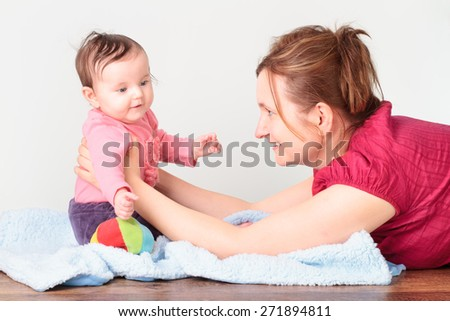 Woman lying on the floor and playing with her little baby girl - stock photo