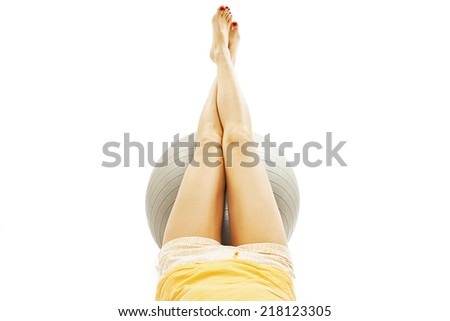 Woman lying on the floor with raised legs on pilates ball. Isolated on white background  - stock photo