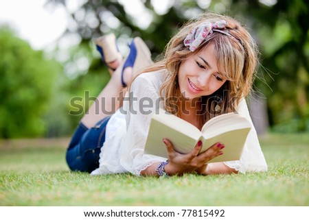 Woman lying on the grass reading a book - outdoors