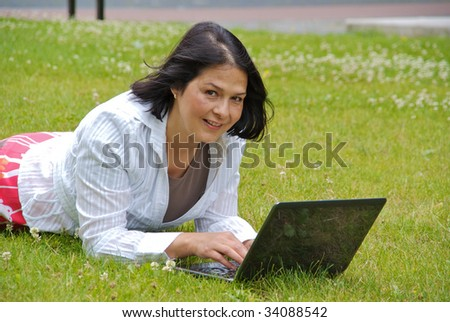 Woman lying on the grass, working wireless on laptop. Focus on woman.