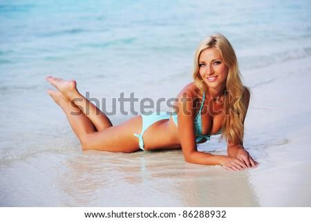 woman lying on the sand the ocean coast - stock photo