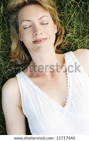 Woman lying outdoors sleeping - stock photo