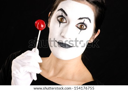 Woman made up in white face holds red sweet lollipop