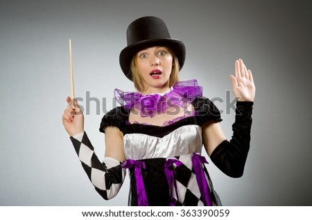 Woman magician doing her tricks with wand - stock photo
