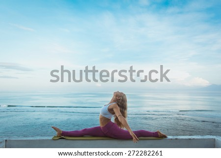 Woman make morning yoga near the sea with blue sky on background