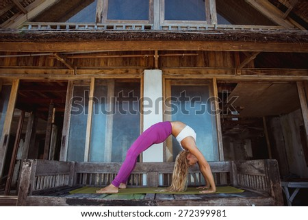 Woman make morning yoga stretching exercise near the wooden house, pose of bridge - stock photo