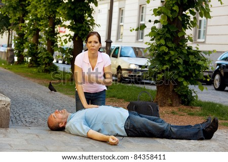 Woman makes first aid for a man with heart attack in the street - stock photo