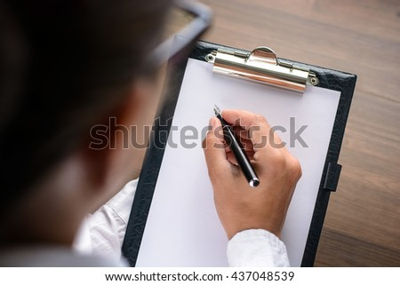 Woman makes notes in a notebook (tablet). With vignette.
