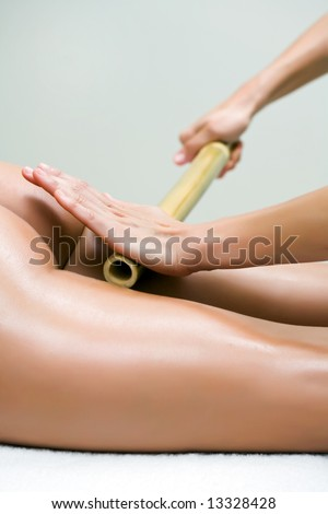 woman making a bamboo massage in the back - stock photo