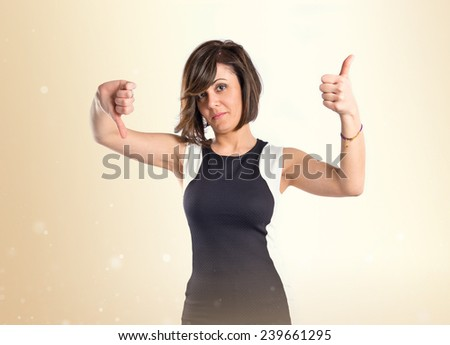 Woman making a good and bad signs over ocher background  - stock photo