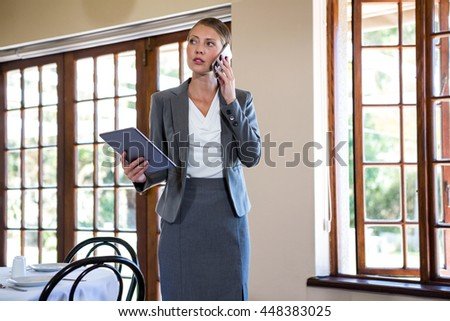 Woman making a phone call in a restaurant - stock photo